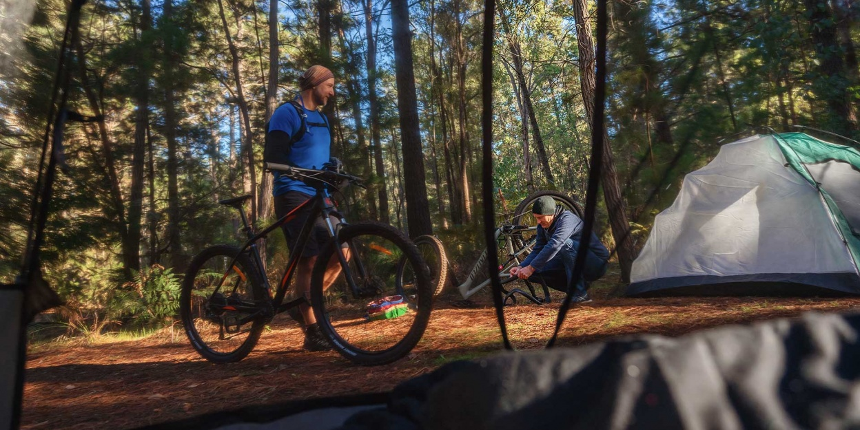 Lane_Poole_Reserve_Camping_Mountain_Bikes_Friends_Men_Tents_Fixing_Bike_Though_Tent_Net-credit-Josh-Cowling